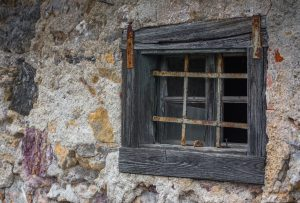 A window on an old rustic house in a village with broken glass